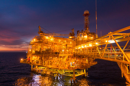Offshore oil and gas rig platform with beautiful sunset time or twilight time in the gulf of Thailand for business industrial concept. Standard-Bild