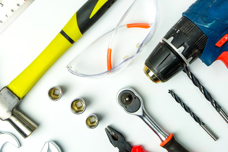 Set of construction tools on white background as wrench, hammer, pliers, socket wrench, spanner, tape measure, electric drill,safety glasses, screwdriver.