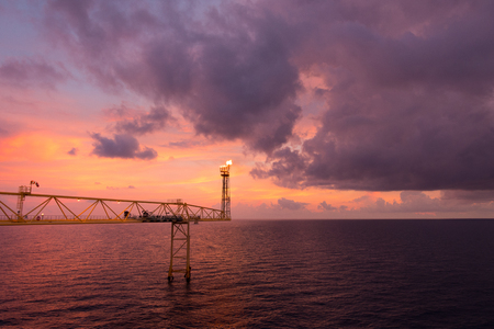 Flare stack and flare bridge while burning toxic gas and release over pressure of production process in sunset time.