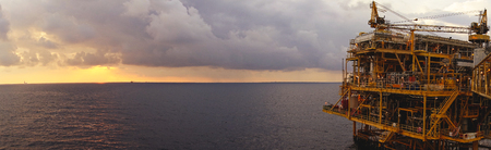 Offshore oil and gas rig platform with beautiful sunset time with storm of clouds in the gulf of Thailand for business industrial concept panorama view. Stock Photo