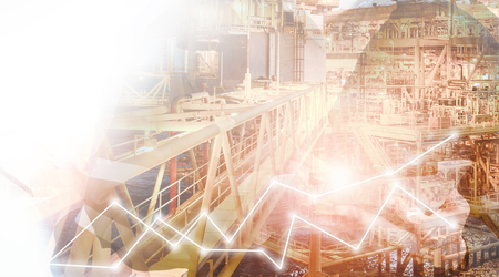 Double exposure of hand using tablet with offshore oil and gas platform background with stock trading graph for oil and gas business industry concept.