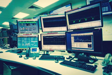 System IT w pokoju kontrolnym z wieloma monitorami w zaawansowanym technicznie obiekcie, który działa w zakresie nadzoru, sieci neuronowych, eksploracji danych.
