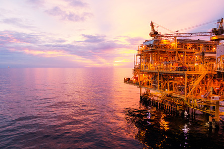 Offshore construction platform for exororation and production oil and gas with bridge in evening time for power energy of the wolrd concept. Reklamní fotografie