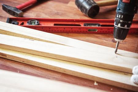 Eigenbau mit Bohrmaschine. Professioneller Tischler, der mit Holz und Bauwerkzeugen arbeitet.