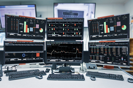 Display of Stock market quotes and chart in monitor computer room with business office equipments .business and money concept, panorama photo.