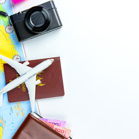 Travel accessories costumes concept for summer vacation trip. Passports, luggage, map, smartphone,sun glasses,camera, note pad, jean on white.