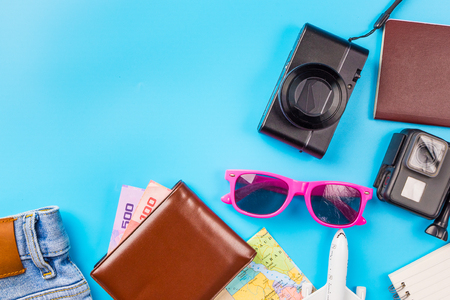 Travel accessories costumes concept for summer vacation trip. Passports, luggage, map, smartphone,sun glasses,camera, note pad, jean on blue.