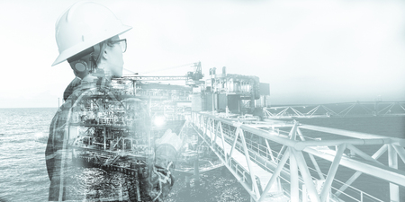 Double exposure of Engineer or Technician woman with safety helmet operated platform or plant by using tablet with offshore oil and gas platform background for oil and gas business concept.