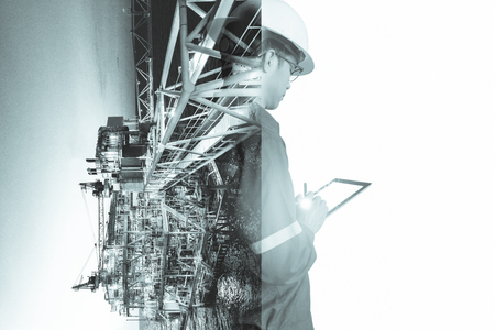Double exposure of Engineer or Technician man with safety helmet operated platform or plant by using tablet with offshore oil and gas platform background for oil and gas business concept. 스톡 콘텐츠 - 125428997