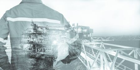 Double exposure of Engineer or Technician man with safety helmet operated platform or plant by using tablet with offshore oil and gas platform background for oil and gas business concept. 스톡 콘텐츠 - 132267767