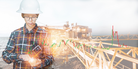 Double exposure of Engineer or Technician woman using tablet with offshore oil and gas platform and stock trading chart background for oil and gas business concept.