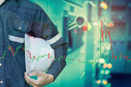 Double exposure of  business man or Engineer holding helmet with industry control room and stock trading chart background for investment business concept.