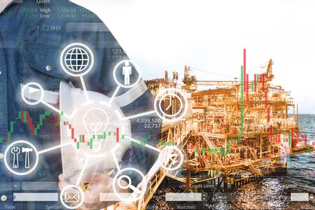Double exposure of  business man or Engineer holding helmet with offshore platform and stock trading chart background for oil and gas business concept.