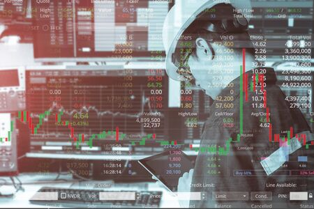 Double exposure of business man or engineer using tablet with stock trading room and stock trading chart background for investment business concept.