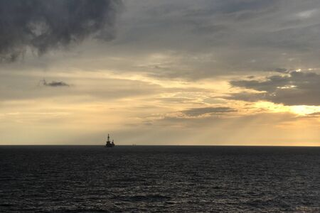 Drilling rig in the sea for exploration and production oil and gas in evening time for power energy of the world concept