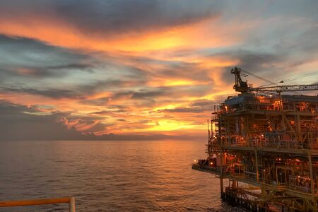 Offshore construction platform for exploration and production oil and gas with bridge in evening time for power energy of the world concept.