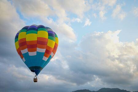 Coroful Mongolfiera Volare nel cielo con nuvole e sfondo di montagna. Archivio Fotografico