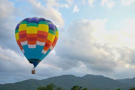 Coroful Balon na gorące powietrze latające na niebie z chmurami i górskim tłem. Zdjęcie Seryjne