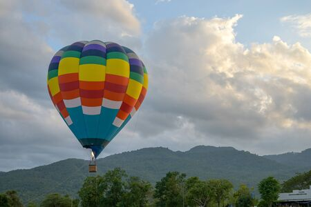 Coroful Hot Air Ballon Flying In The sky with clouds and mountain background. Stock fotó