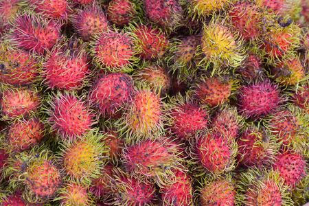 Healthy fruits rambutans upper view on local market sweet Thai fruit.