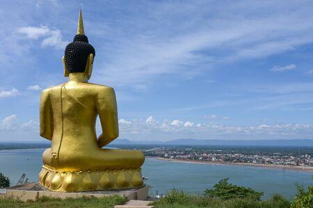 The big golden Buddha statue of Phu Salao temple with Mekong River flows through the Pakse city,Laos. Foto de archivo - 140904320