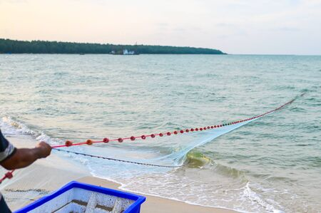 Close view of some blue fishing net floaters on the beach with boat and human while laying nets on the sea.