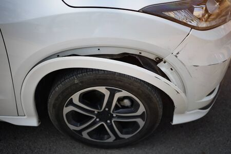 white car has a small bump crash, due to a slight with front-end collision,waiting for insurance contact.