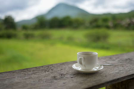 Cup of coffee or tea on a wooden table over mountains landscape and rice field with sunlight. Beauty nature background.