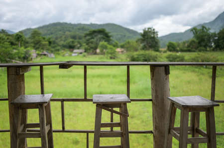 wooden table and chair for drink coffee and watching view of mountain farm landscape in sunlight.