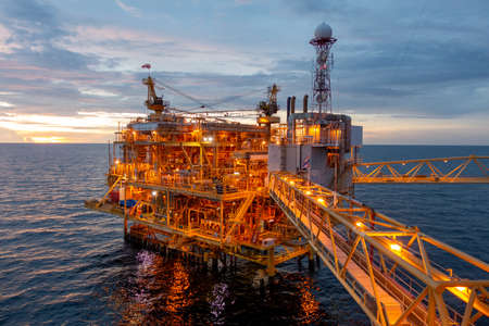 Offshore oil and gas rig platform with beautiful sky in sunset time for business industry concept.