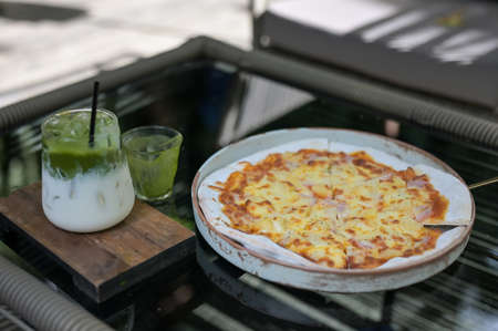 whole italian pizza with ice green tea on wood table with ingredients.