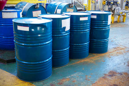 Blue oil drums in front of a factory or industrial plant for oil and gas industry concept.