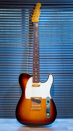 Sunburst electric guitar telecaster shape (gold hardware) on woden table in the room. businoess and music concept. Wallpaper or background.