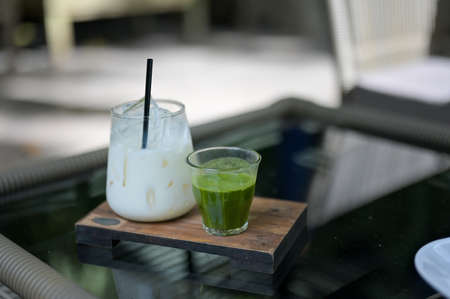 Ice green tea cup and glass jars of milk on the wooden table in the cafe background with copy space.