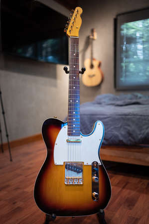 Sunburst vintage electric guitar (gold hardware) on wooden table in the room. business and music concept. Wallpaper or background.