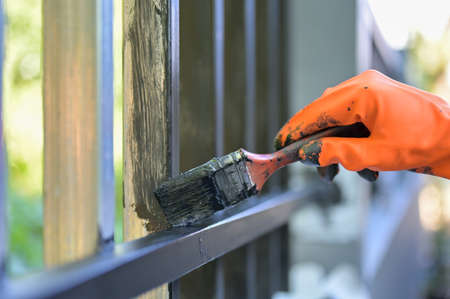 Worker painting steel with paint brush and orange gloves selective focus on hand.