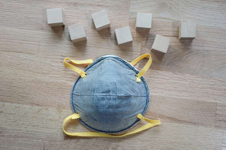 N95 mask On the wooden table with group of wooden cube for input wording,Helps prevent corona virus infection concept. 스톡 콘텐츠
