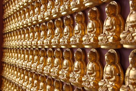 nonthaburi: hundreds of buddha images attached to wall, chinese temple in thailand