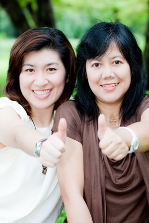 thai teen: portrait of happy women outdoor give thumps up Stock Photo