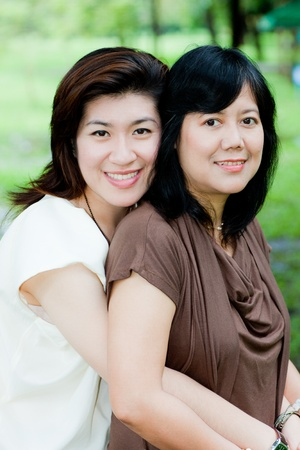 portrait of smiling two women embracing outdoor Stock Photo