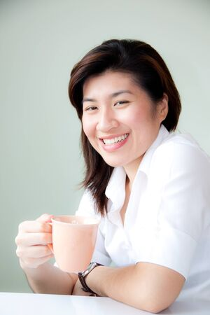 smiling young asian woman holding a cup photo