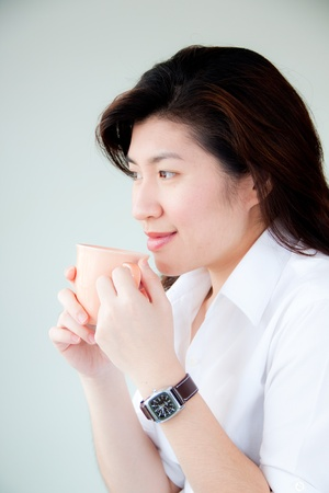 smiling young asian woman holding a cup