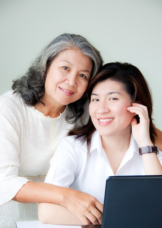 smiling two asian women with notebook photo