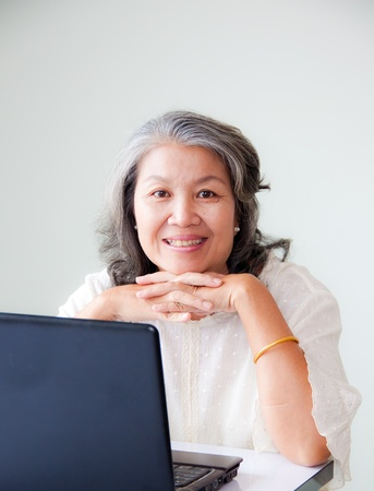only one senior: smiling senior asian woman with notebook