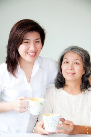 grandparent: two asian women holding cups Stock Photo
