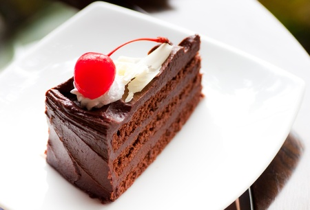 soft chocolate cake on white dish with red cherry