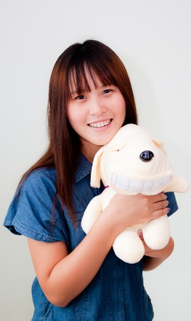 asian teenager smiling with her doll on white background photo