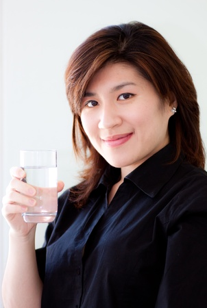 asian woman holding a glass of pure water