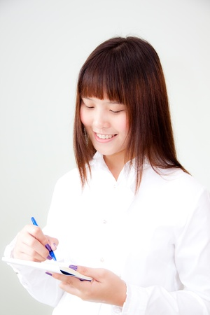 young asian woman writing on her notebook