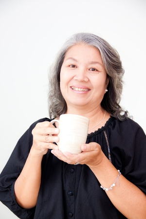 senior asian woman holding a cup photo